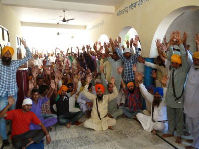 Villagers raise their hands in support of the arrested brothers at a gurdwara in Panjgrain Khurd village on Wednesday