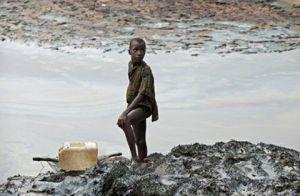 Дитина на забрудненому нафтою березі в Гоі