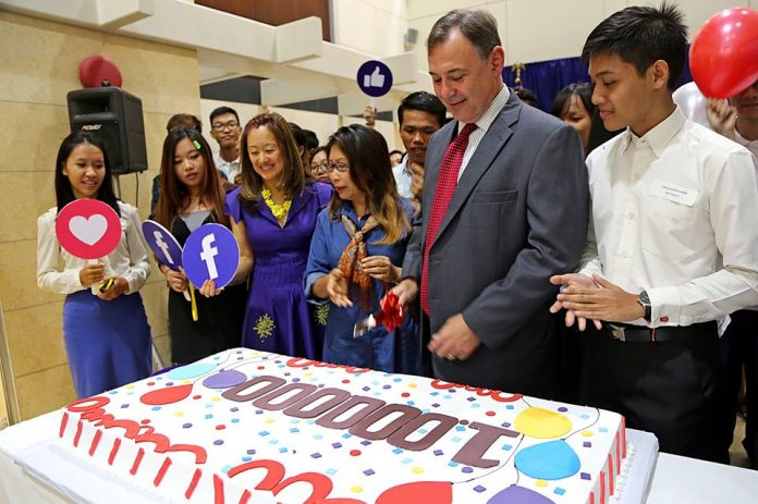 Ambassador Heidt cuts the cake for the participants.