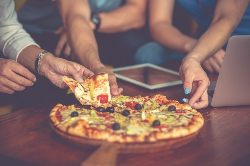 Group of people eating pizza around a table