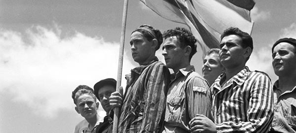 Jewish men standing together with flag of Israel