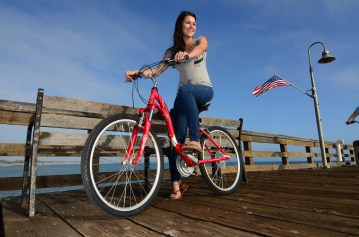 A rider taking a KHS comfort bike along the boardwalk