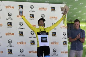 Elevate KHS pro cycling's James Piccoli on the Tour of Utah podium wearing the yellow leaders jersey after winning the first stage of the race.