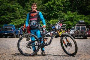 KHS Pro MTB team rider Nik Nestoroff standing behind his KHS DH 300 bike.