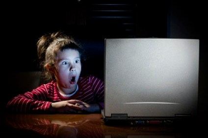 Child with surprised face in front of laptop.
