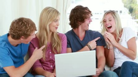 stock-footage-happy-friends-laughing-while-looking-at-a-laptop-in-a-living-room