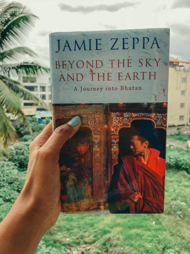 A girl holding the book Beyond the sky and the earth in her hand