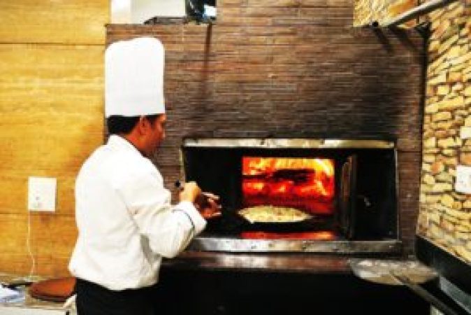 Chef getting ready to bake an Italian pizza in a woodfire oven