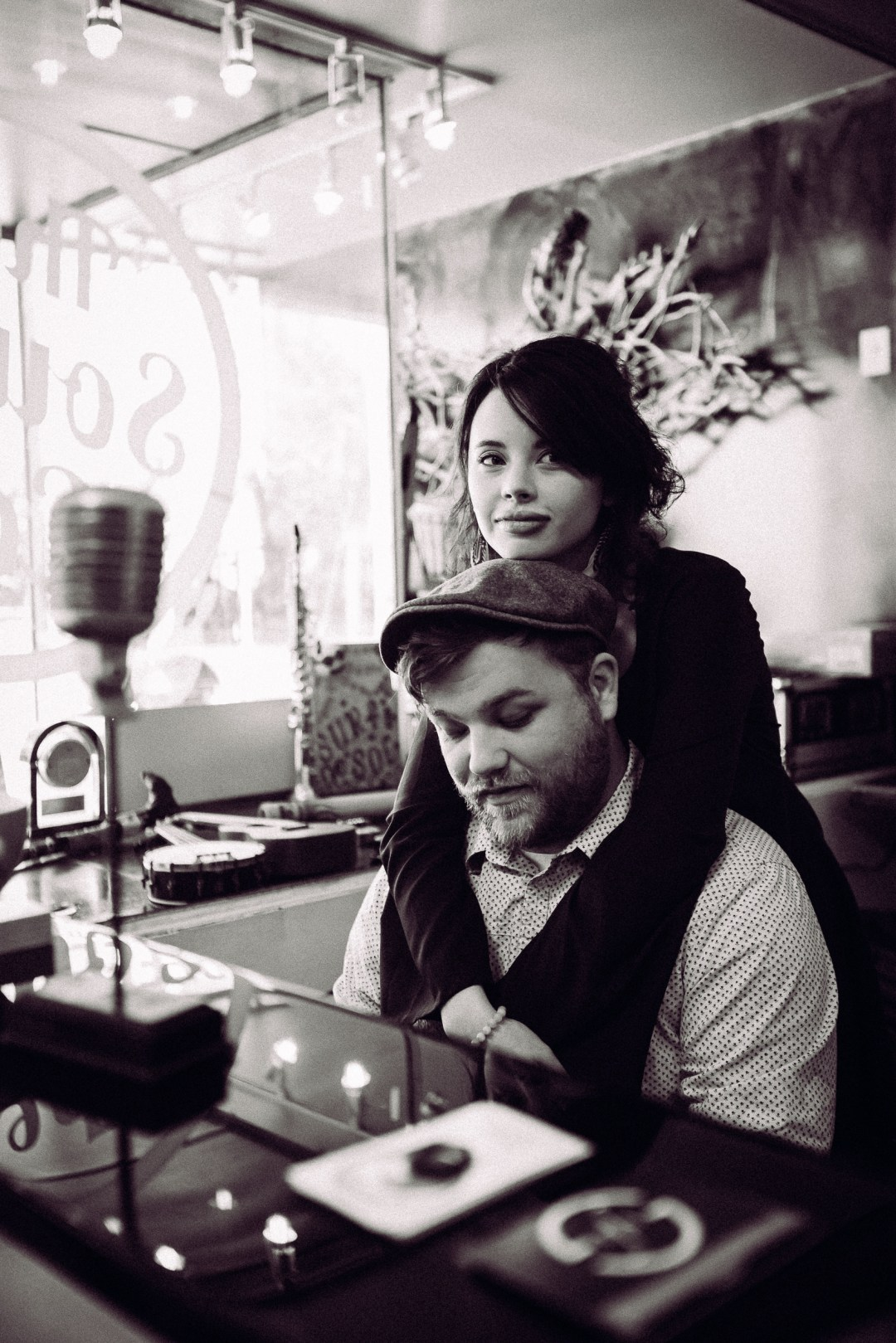 black and white photo of a couple sitting at piano in a coffee shop