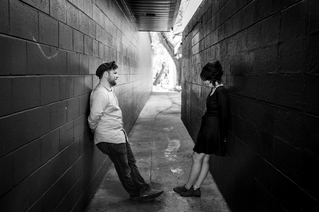 black and white photo of couple in alley leaning on opposite walls