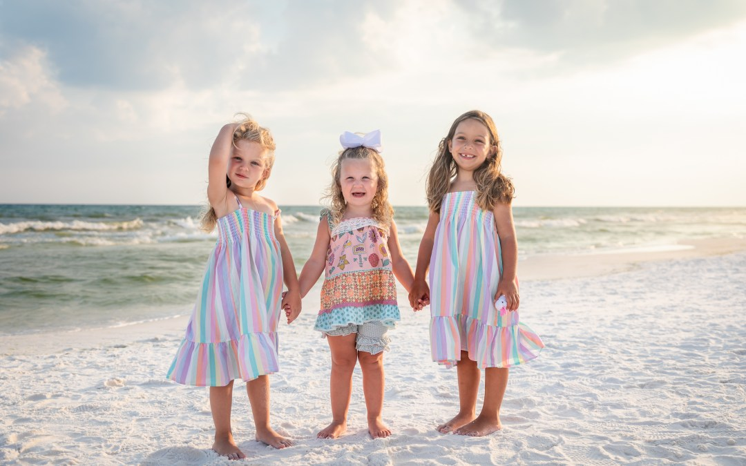 three young girls holding hands on the beach
