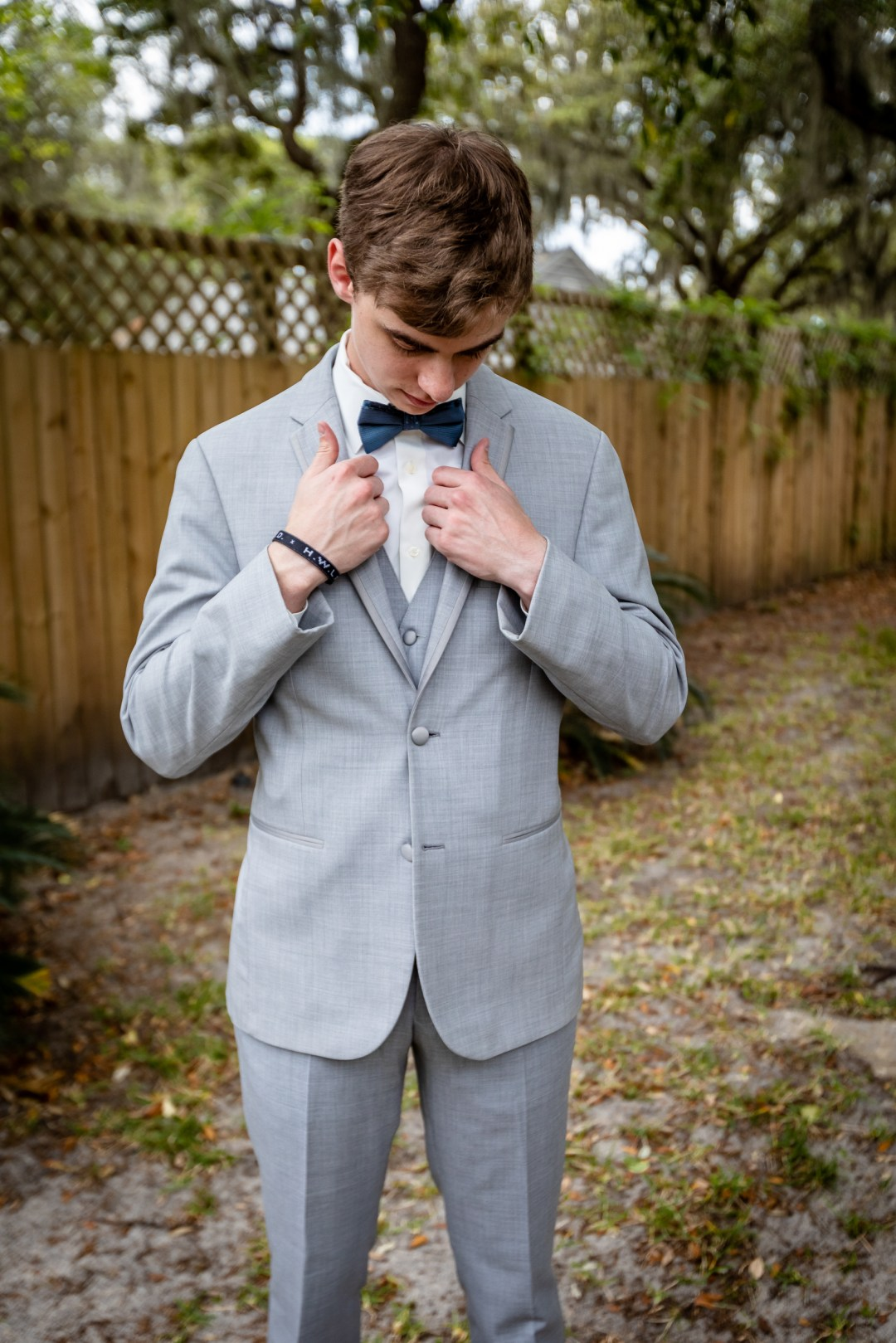 groom adjusting tuxedo jacket on wedding day