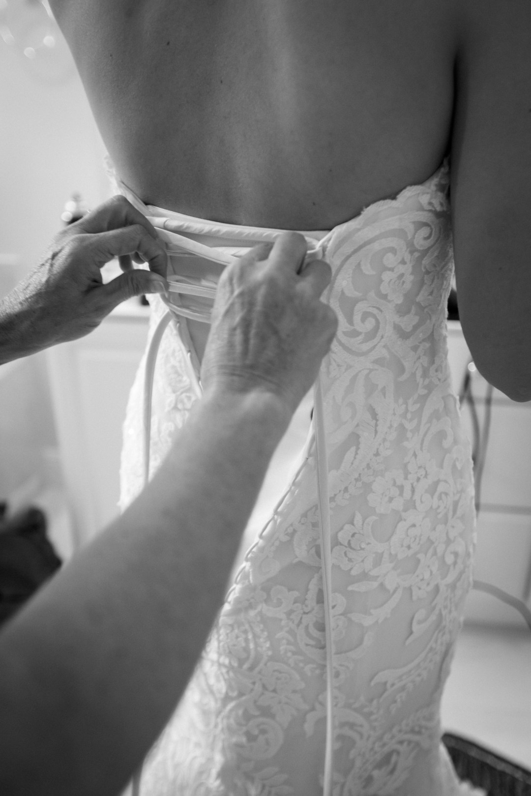 photo of bride lacing the back of her wedding dress