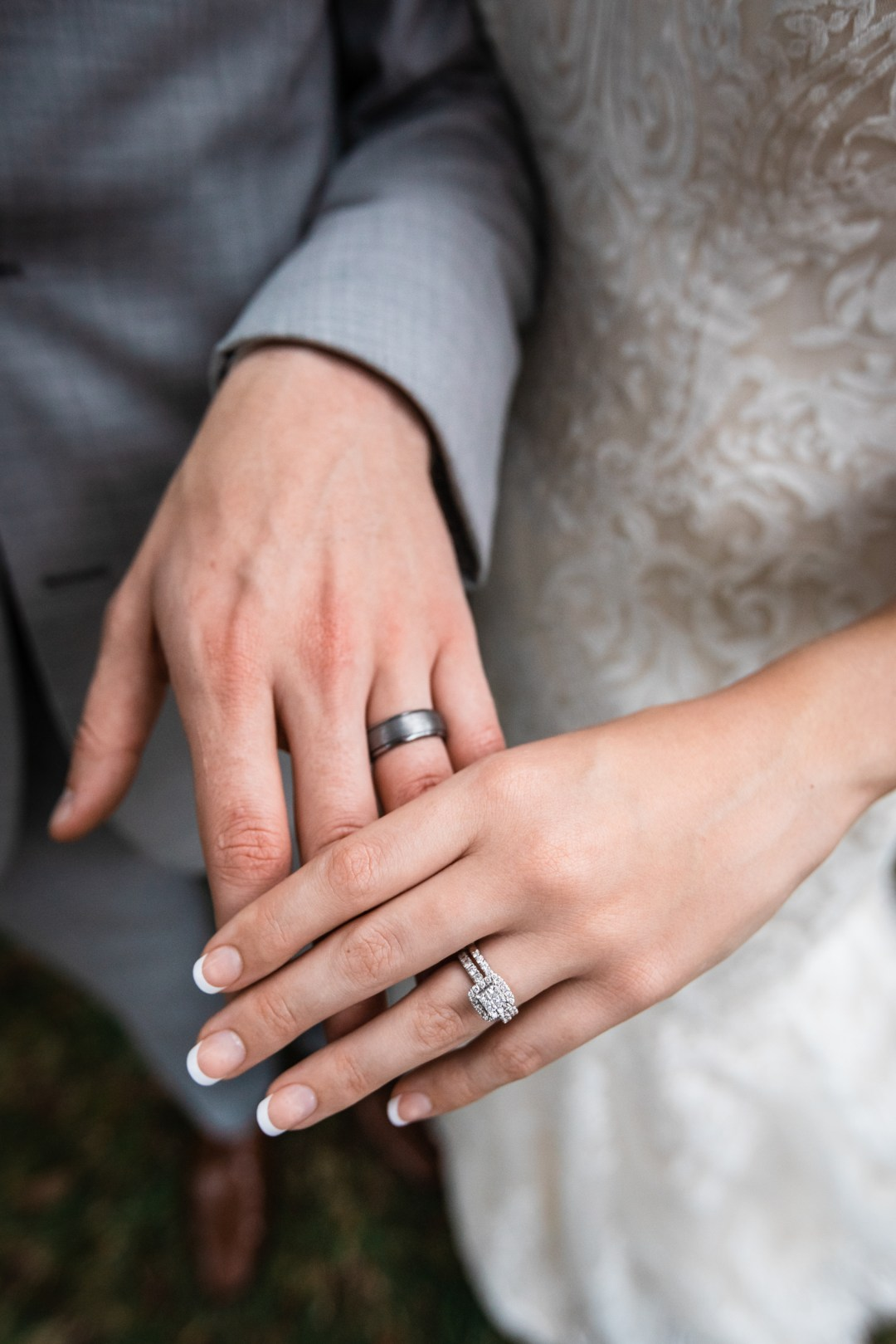 photo of bride and groom hands wearing wedding rings