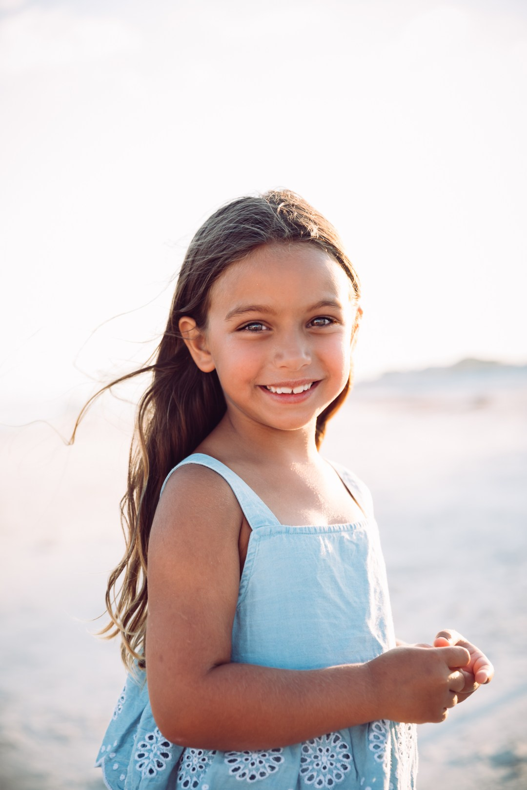 young girl in blue dress on the beach