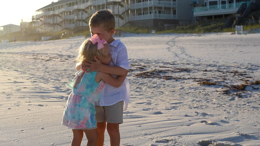 brother and sister hugging on the beach