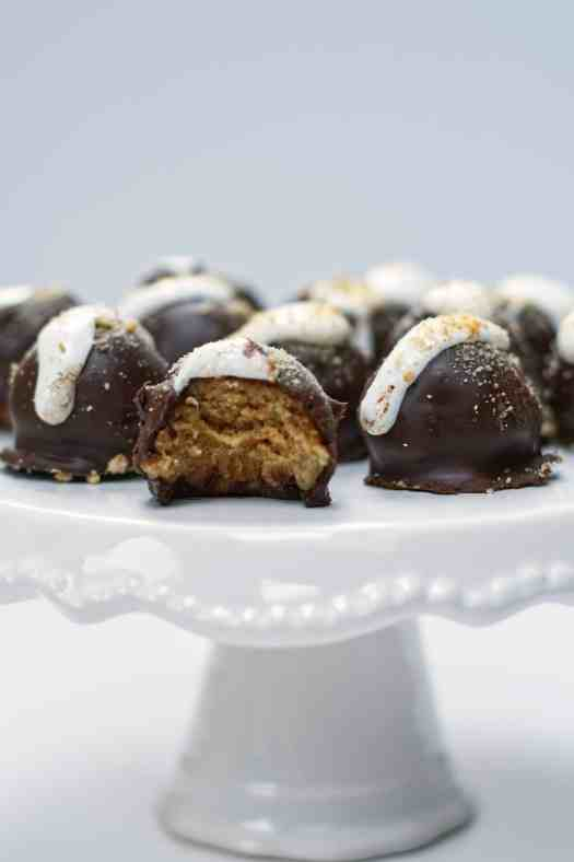 S'mores Truffles are the summer combo we all love rolled up into one perfect bite | kickassbaker.com #smores #truffles #smorestruffles #summerrecipes #easyrecipes #kickassbaker #summertime #grahamcrackers #chocolate #marshmallow #marshmallowfluff