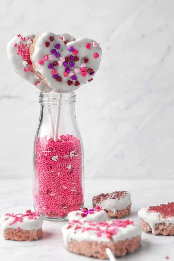 White Chocolate-dipped Rice Krispie Treats   kickassbaker.com #valentinesday #treats #vday #love #ricekrispietreats #ricekrispies #whitechocolate #almondbark #sprinkles #kidstreat #funwithkids #easyrecipes #forkids #nutfree