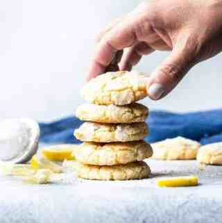 Lemon Crinkle Cookies stacked grabbing one from the top with lemon pieces scattered about | kickassbaker.com