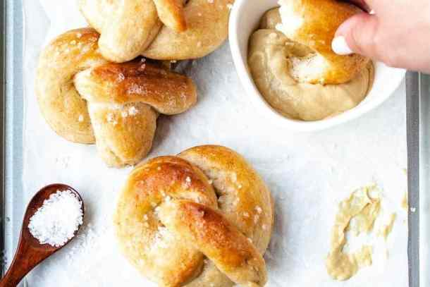 Soft pretzels on a tray being dipped in mustard