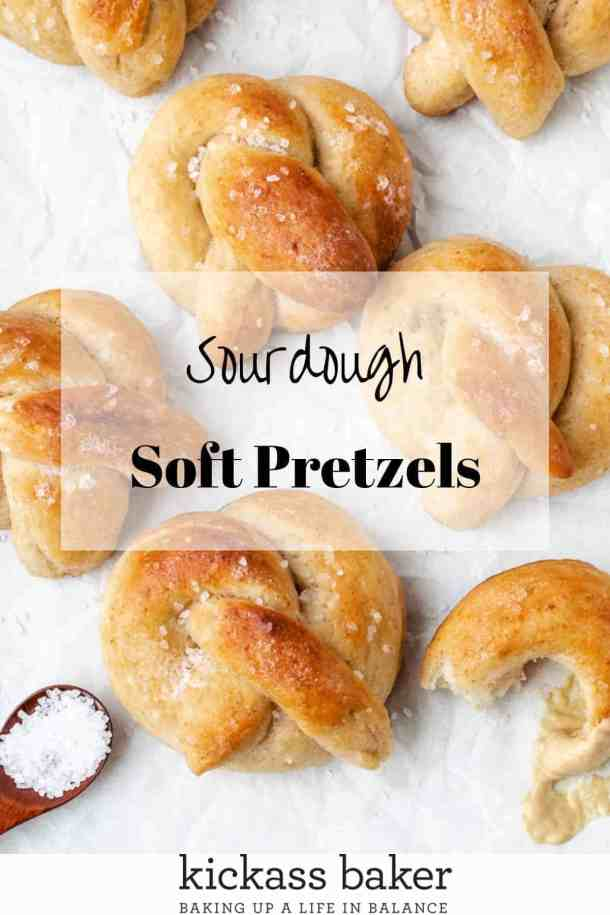 Sourdough soft pretzels on a sheet tray with salt and mustard off the side, showing the texture and size of the pretzels
