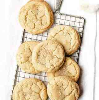 Overhead shot of Soft and Chewy Sugar Cookies on a cooling rack with a glass of milk behind