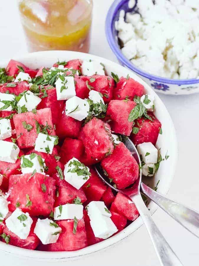Watermelon salad with feta cheese in bowl behind and dressing in jar