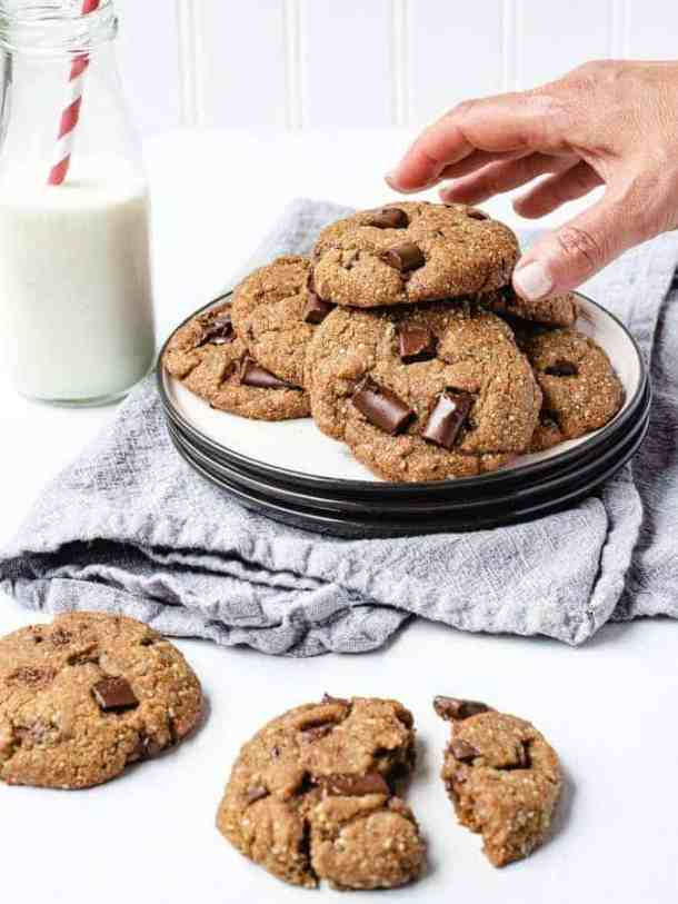 Reaching for a paleo chocolate chip cookie from a stack on a plate