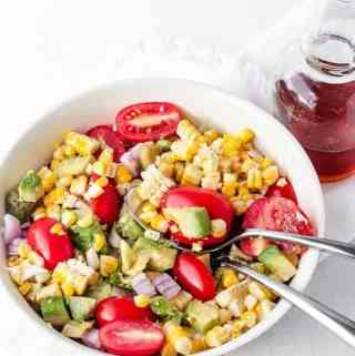 Avocado Corn Tomato salad with red onion ready to be eaten with two spoons in the bowl and dressing on the side ready to be poured in