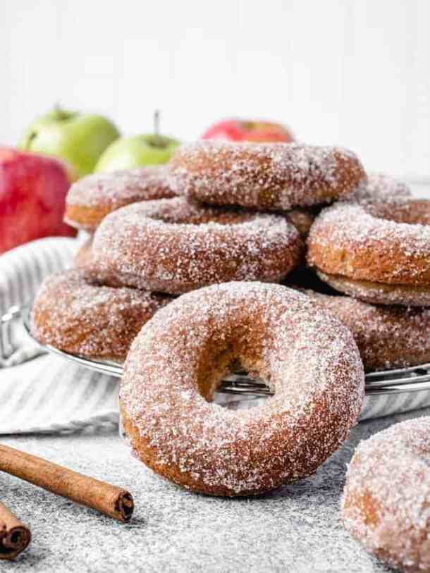 pile of baked apple cider donuts on a wire rack with apples in the background and cinnamon sticks in front