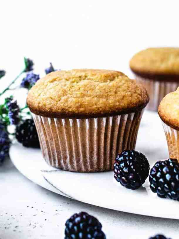honey corn muffins with blackberries sprinkled around