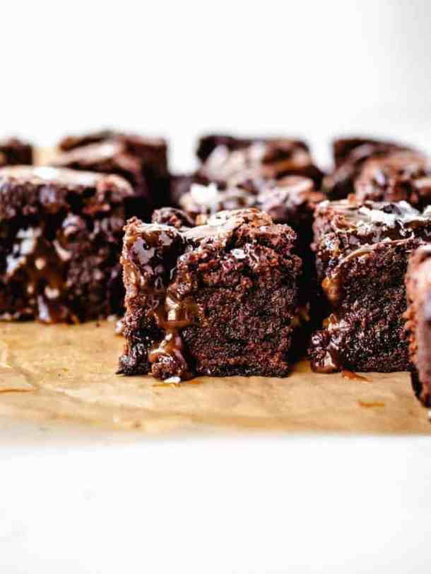 Close up image of salted caramel brownies on piece of parchment paper