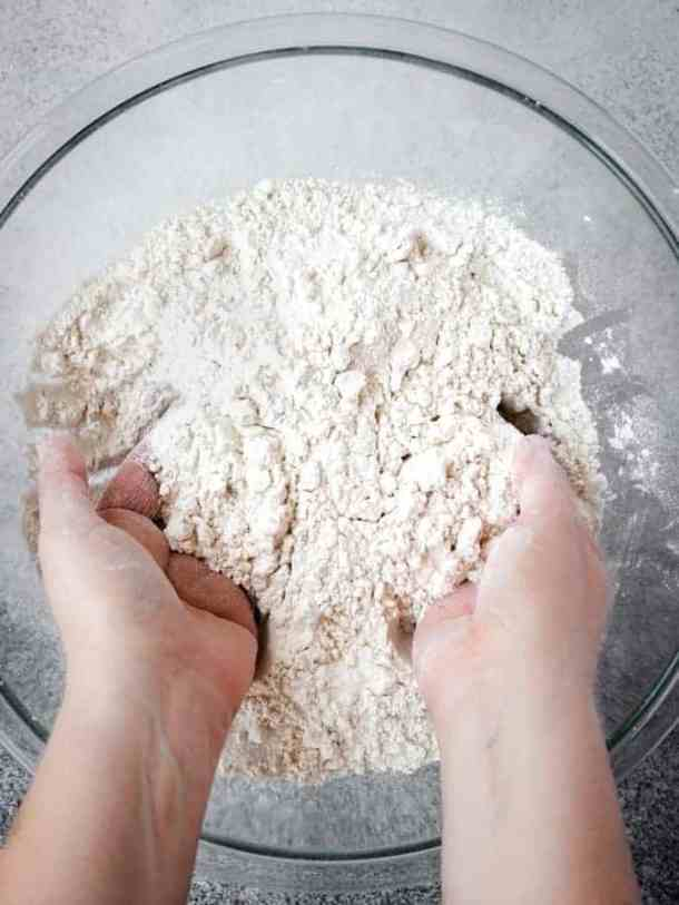 Mixing dry ingredients for Irish soda bread with hands