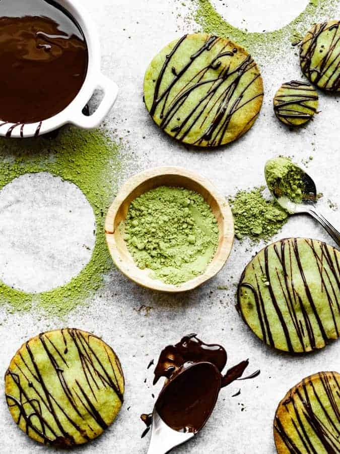 overhead of matcha green tea cookies and melted dark chocolate and matcha powder on a baking sheet