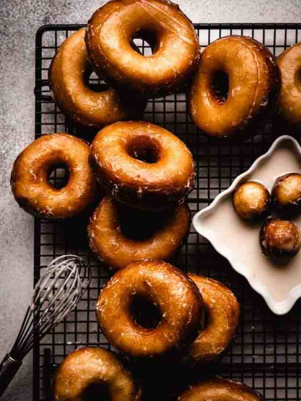 glazed donuts on a wire cooling rack with a whisk and donut holes sitting in glaze