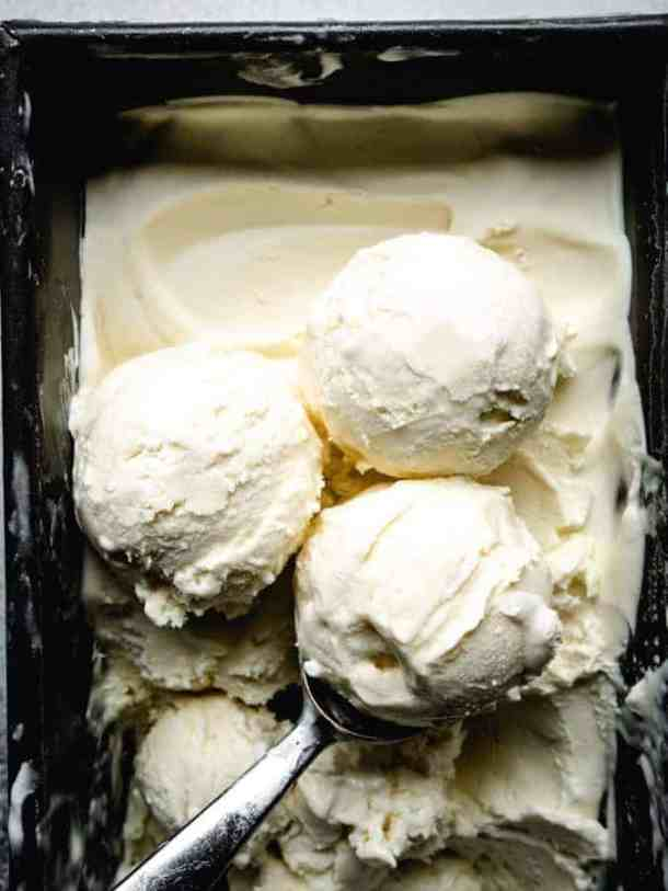 scoops of homemade vanilla ice cream in a pan with an ice cream scoop