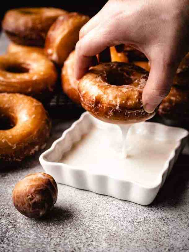 Dipping a homemade yeast donut in glaze with some dripping off