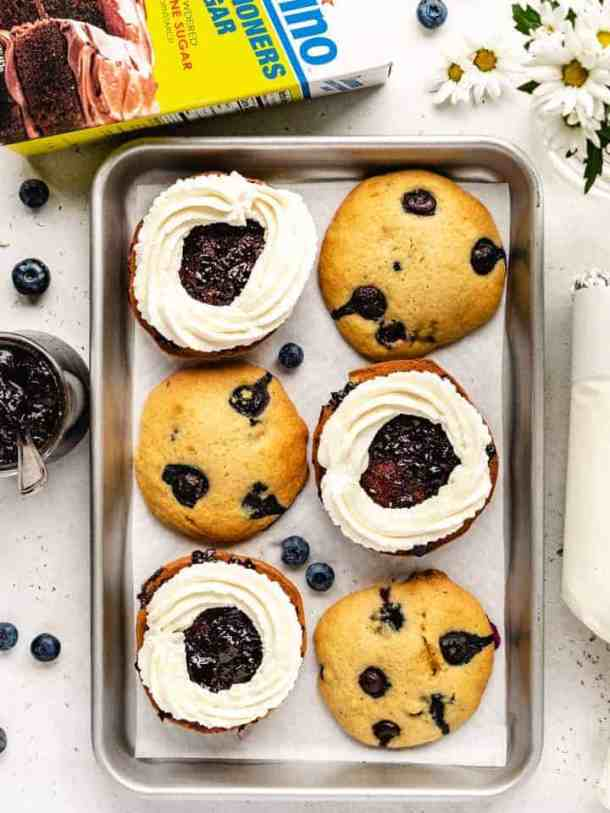 blueberry whoopee pies getting assembled with whipped cream and blueberry jam filling