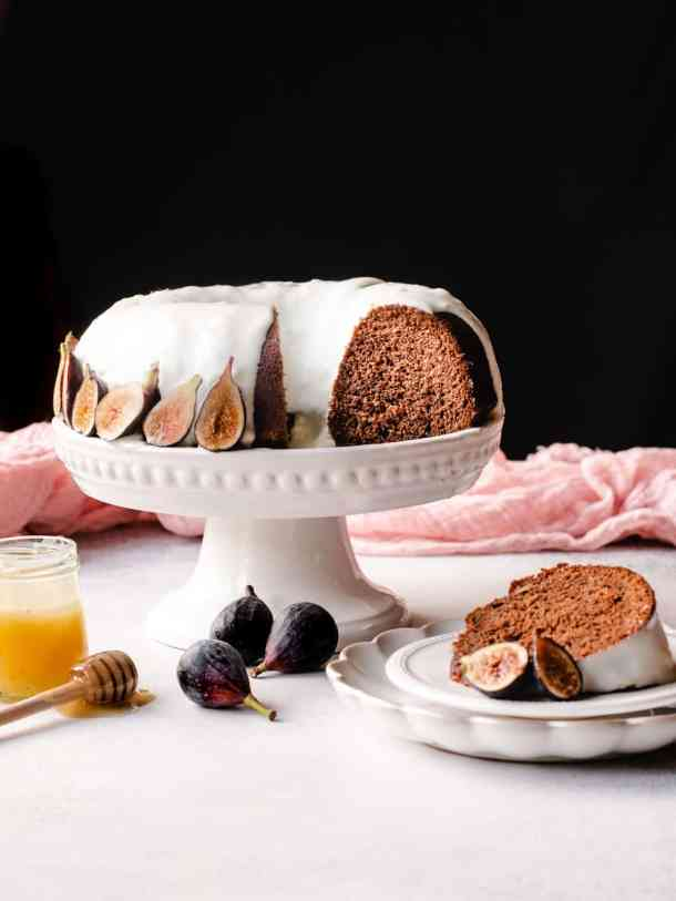 honey cake on a cake stand with figs and honey