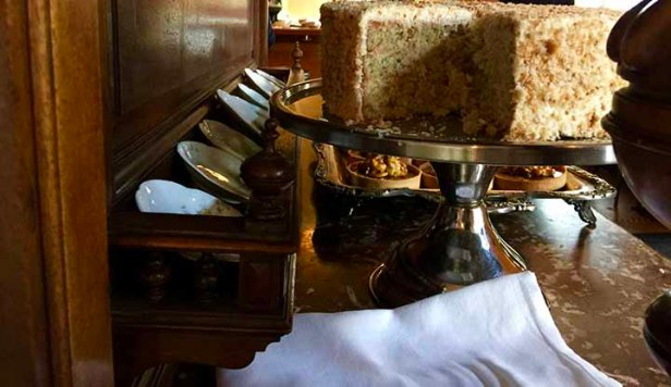 Some of the desserts are displayed upon a silver platter atop an antique piece with a marble top.