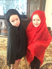 The twins entertain themselves with their own scarves.