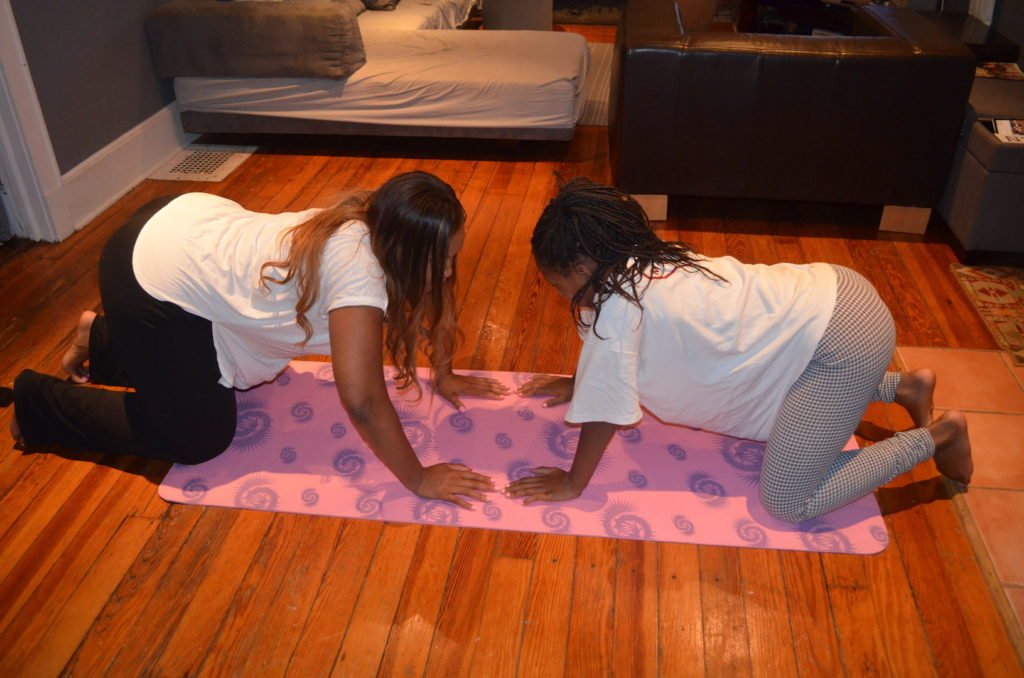 Mother and daughter practice cow yoga position