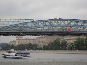 People sitting on a bridge over the Moscow River