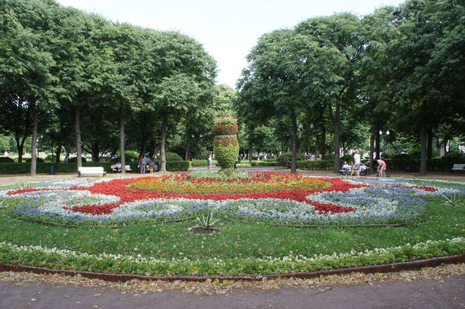 A circular flowerbed with a swirly pattern made of different coloured flowers, especially red. In the middle an urn made of a clipped bush rather than stone rises up, with spiky leaves growing out of the top. The flowerbed is surrounded by trees and benches, and there are people sitting or walking around it.