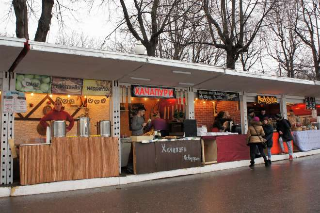 There are five food stalls. The signs are all in Cyrillic. The nearest has tea urns with bread snacks a bit like pretzels handing. Stallholders are busy preparing food or standing looking out. One customer is leaning on the stall and chatting to the stallholders. It has been raining and the customers are wearing warm coats, hats and boots.