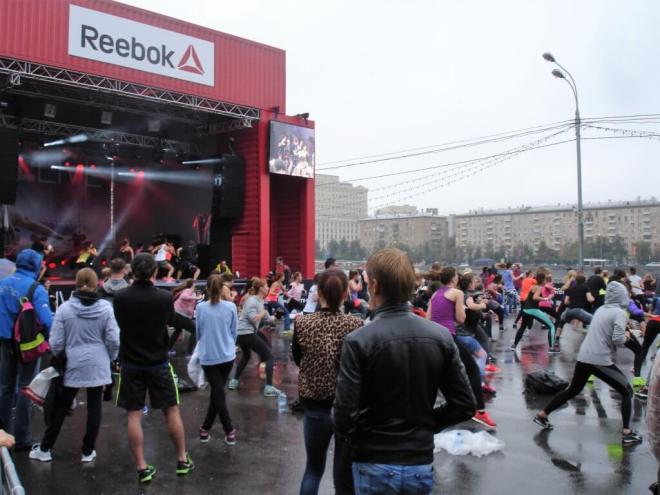 To the left there is a red stage with Reebock written over it. On stage people in exercise gear demonstrate moves. In front of the stage, some people in aerobics gear are copying them, while others watch. They all have their back to the camera. It is a rainy day, and everyone is dressed for that weather.