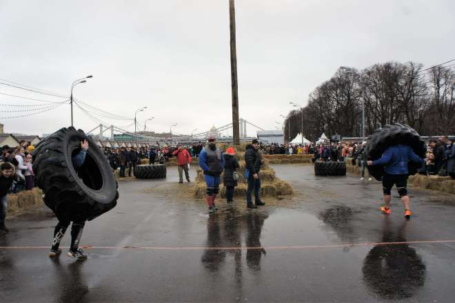 Two large men have picked up a large tractor tire and are carrying them in parallel in a rage. Straw bales mark the area they are racing in. Other people are standing and watching them. It is a wet day.