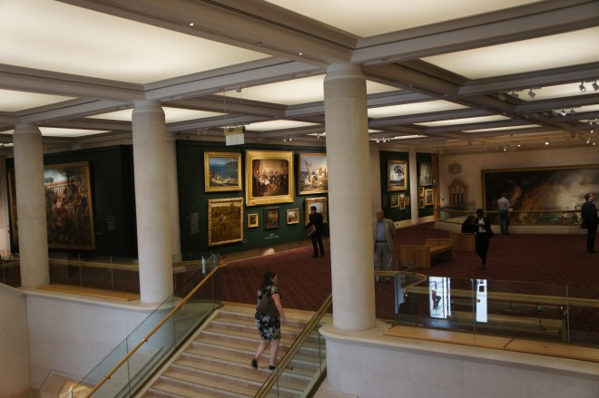 A gallery in the Guildhall Art Gallery. There is a woman walking up some stairs bewteen colums to a large open plan room with a red carpet, green walls and gold framed paintings. The ceiling is white glowing panels.