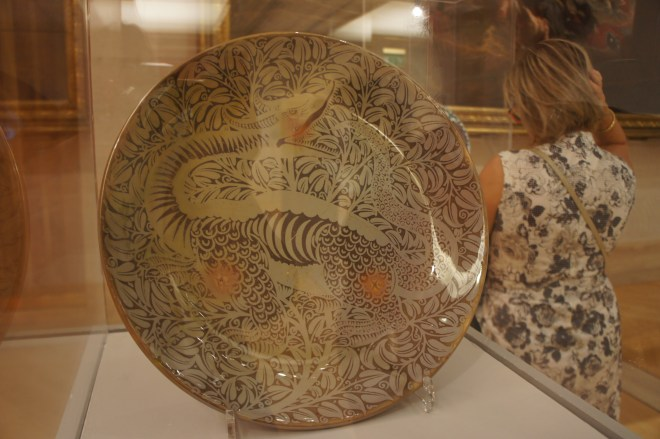 A large plate with a brown styalised dinosaur and foliage design. A woman in a floral dress stands in the background with her back to us.