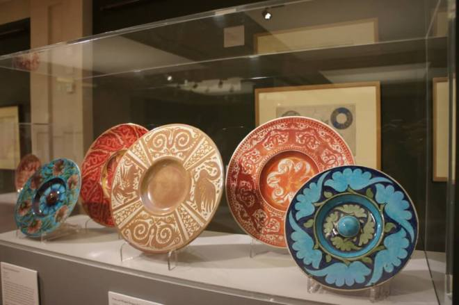 A selection of William de Morgan plates with styalised animal and plant designs in blue, red and brown.